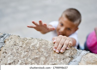 boy overcoming efforts. striving for a goal. conquering the top of the mountain. achieve a difficult goal. boy hanging on the wall.