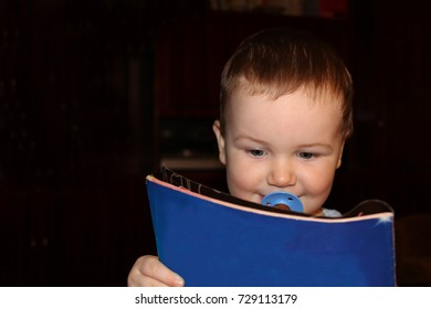 Boy with pacifier reads the journal