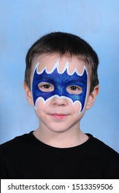 A boy with a painted face in the image of Batman in a Studio in Moscow on a blue background on January 4, 2015