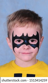 A boy with a painted face in the image of Batman in a Studio in Moscow on a blue background on February 28, 2015