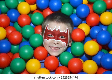 A boy with a painted face in the image of Batman lies in a dry pool with colored balls sticking out his face in Moscow September 21 2014