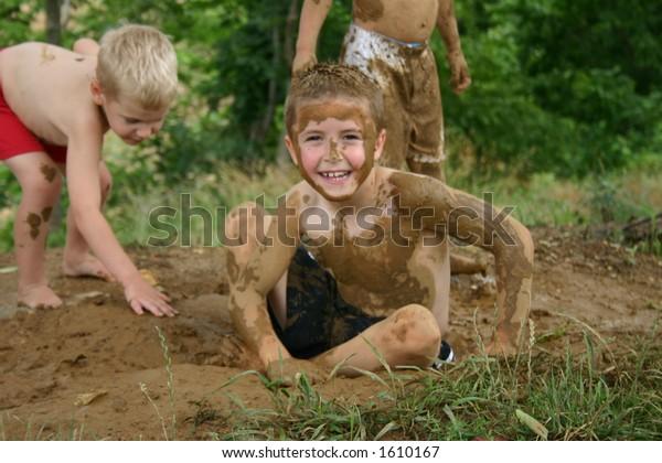 Junge mit Schlamm gemalt, sitzend im Schmutzloch, mit anderen Jungen auf Hintergrund
