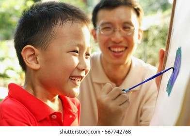 Boy painting on easel, father next to him, smiling