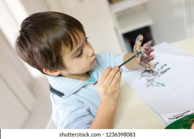 boy painting a paint in house on white table