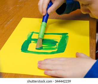 Boy paints green square on yellow paper creatively on wooden table.
