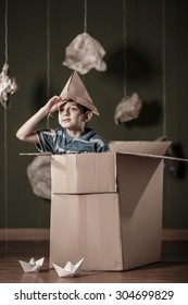 Boy with paper hat playing in carton box