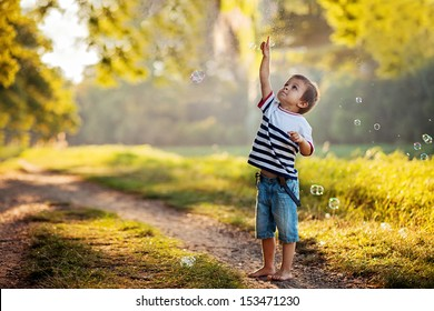 Boy in a park, chasing bubbles