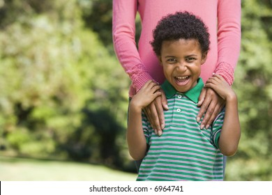 Boy in park making funny expression with mother's hands on shoulders.