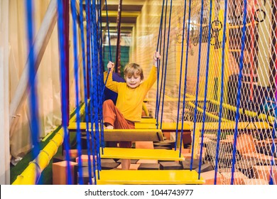 The boy passes the obstacle course in the sports club