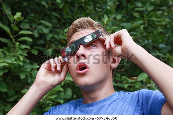 Boy peeking at the sun during a solar eclipse