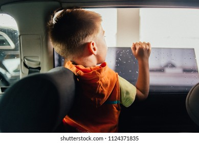 boy peeks out of the car