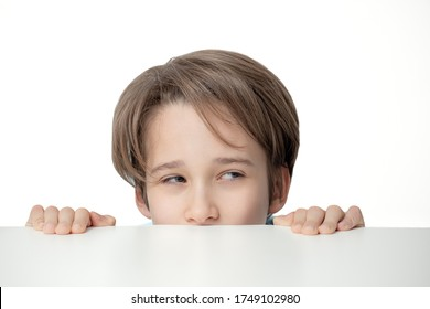 boy peeping from behind a white table, the  portrait  of boy looks out, a sly look,  free copy space,