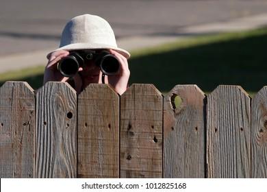 Boy peering over fence with binoculars