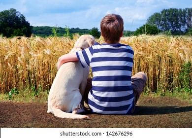 Boy with pet dog, corn field in background