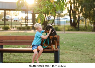 Boy and pet rottweiler dog sitting on park bench at playground in Rockhampton, Queensland