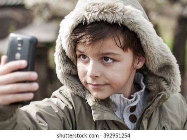 boy photographing himself with a cell phone