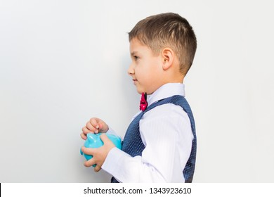 boy with a piggy Bank in his hands on a white background. side view