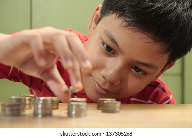 Boy and a Pile of Coins A photo of a boy looking at a stack of coins and stacking them.