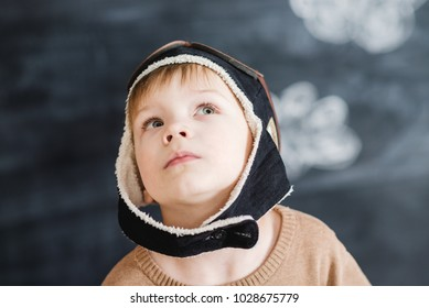 the boy in the pilot's cap with glasses playing a paper plane