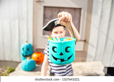 boy in a pirate costume holds a bucket with inedible gifts.  Teal Pumpkin Project. Alternative non-food treats for kids with food allergies. the concept of health for children in the Halloween season.