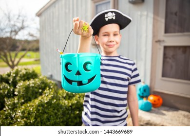 boy in a pirate costume holds a teal bucket in Halloween. trick-or-treat. the concept of health for children in the Halloween season.
