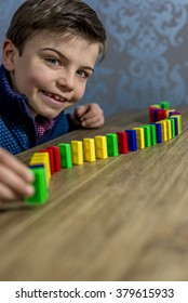 boy placing domino pieces on a table, shallow depth of field