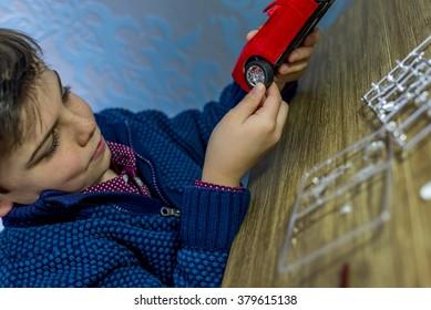 boy placing a wheel on model car, shallow depth of field
