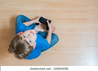 Boy plaing video game with game pad in hands. Flat lay top-down