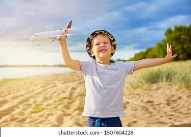 boy with a plane in his hands on the beach