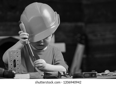 Boy play as builder or repairer, work with tools. Childhood concept. Kid boy in orange hard hat or helmet, study room background. Child dreaming about future career in architecture or building.