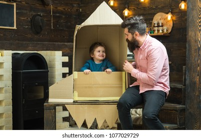 Boy play with dad, father, little cosmonaut sit in rocket made out of cardboard box. Kid happy sit in cardboard hand made rocket. Child boy play cosmonaut, astronaut. Parenthood concept.