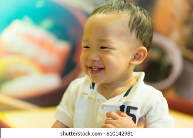 A boy play and eat a noodle.