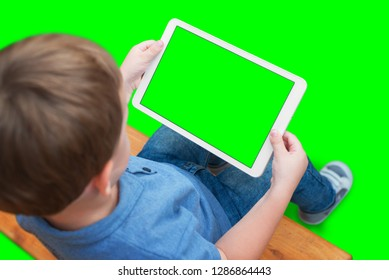 Boy play game or watching video on white tablet. Isolated screen and background in green, chroma key.