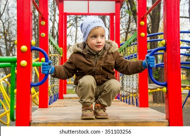 Boy play on playground in cold autumn
