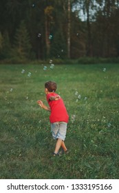 boy play with soap bubbles in park
