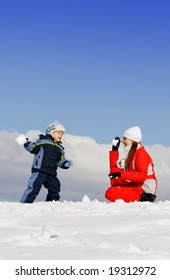Boy played with mother in winter park. Snow. Blue sky