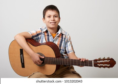 Boy is playing the acoustic guitar on white background