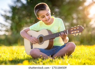 Boy playing acoustic guitar in a summer field in the sunshine
