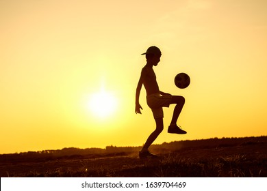 Boy playing with ball in nature in hot evening, silhouette of playing child at sunset in countryside