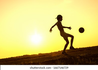 Boy playing with ball in nature in hot evening, silhouette of playing child at sunset outdoors