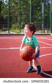 The boy is playing with the ball on the basketball court.Toddler playing basketball