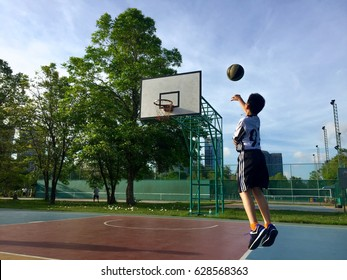Boy playing basketball at the park in the morning.