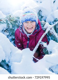Boy playing in big snow in winter. Happy caucasian child playing in snow forest
