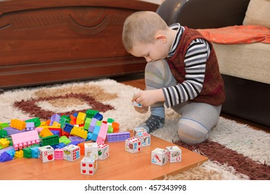 boy playing with blocks and train on the floor