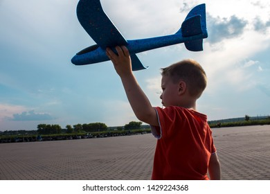 boy playing with a blue airplane in the street against a blue skya