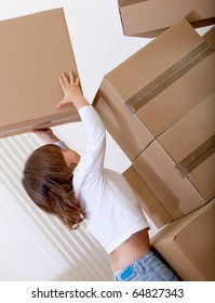 Boy playing with cardboard boxes trying to lift them up