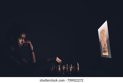 A boy playing chess against a computer