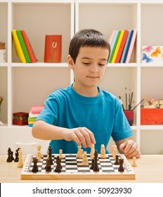 Boy playing chess in the children's room