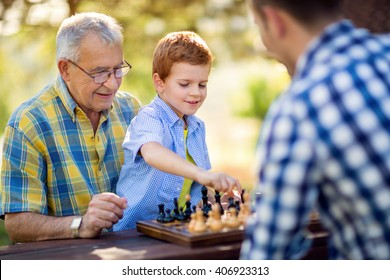 boy playing chess on the table in the park
