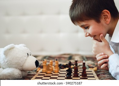 boy playing chess with a Teddy bear